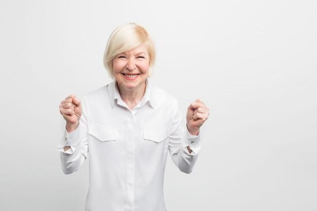 성숙하고 행복한 여자는 기뻐하고 있습니다. 그녀는 나이가 들었을 때 동시에 자신감과 여성 스러움을 느꼈습니다.