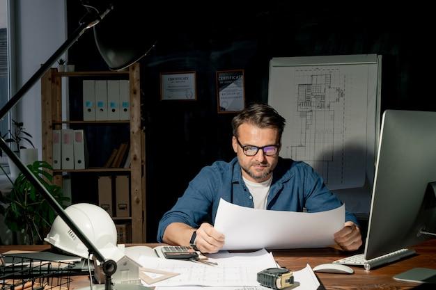 Зрелый архитектор в очках и повседневной одежде смотрит на эскиз на чертеже во время работы в офисе поздно вечером