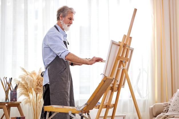 그림에 집중하는 성숙한 예술가 남자, 앞치마를 입은 백인 남성은 예술 창작에 몰두합니다.