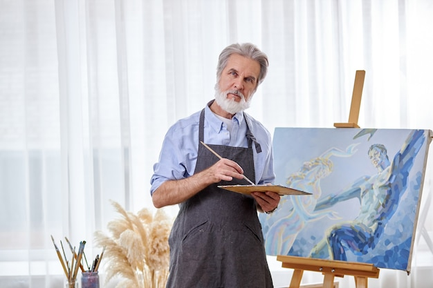 Mature artist with palette and paintbrush in hands while working on canvas