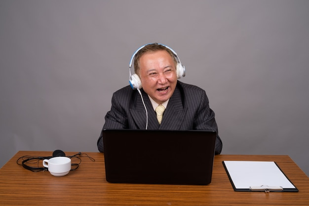 Mature asian businessman sitting with wooden table against gray