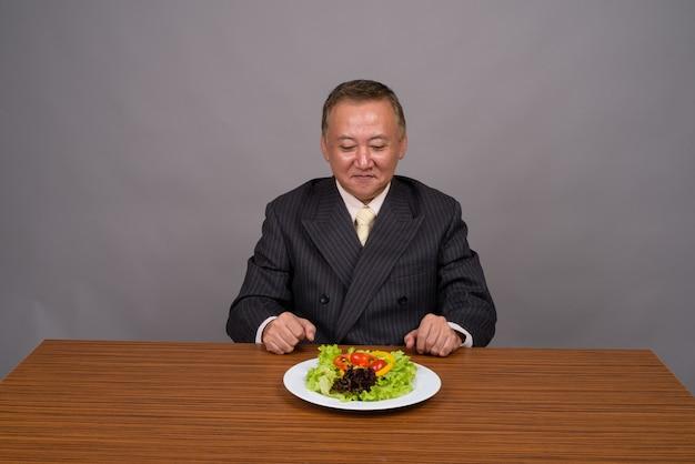 灰色に対して木製のテーブルと座っている成熟したアジアの実業家