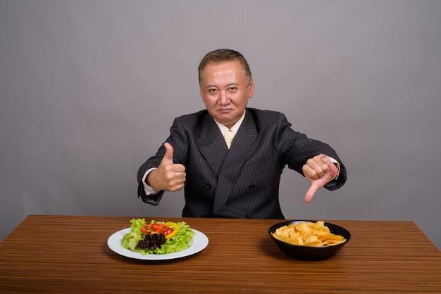 회색에 대 한 나무 테이블에 앉아 성숙한 아시아 사업가