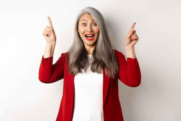 Mature asian businesswoman with grey hair, wearing red blazer and pointing fingers up, smiling surprised, showing promo offer, white background.
