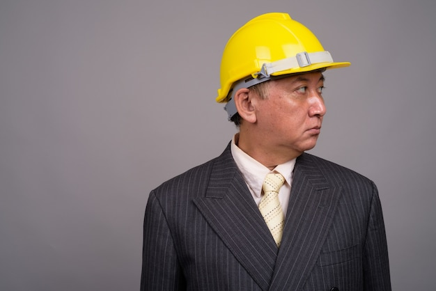 Mature asian construction businessman against gray wall