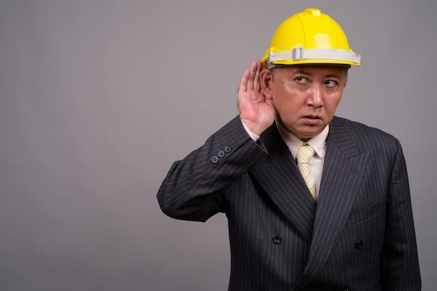 Зрелый азиатский строительный бизнесмен против серой стены