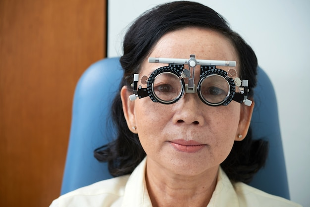 Mature asian lady wearing trial lens frame during eyesight examination