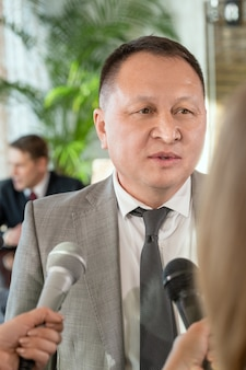 Mature asian male delegate in formalwear standing in front of journalists with microphones and answering their questions during interview