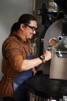 Mature asian man in apron standing next to coffee roasting equipment and checking controls