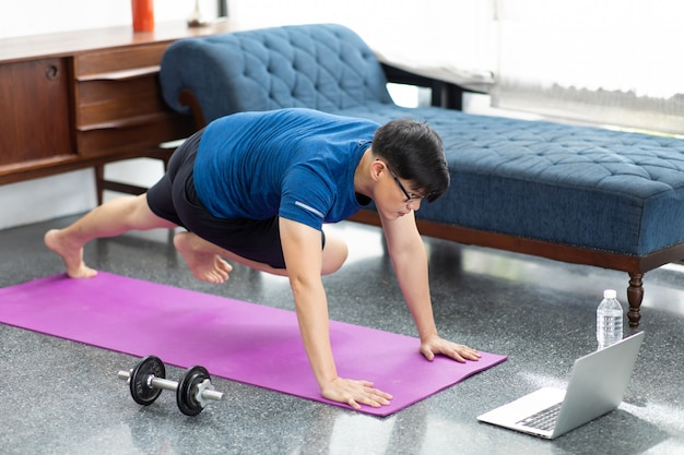 Mature asian man doing exercises at home. workout at home. social distancing.