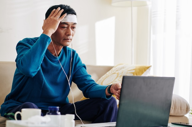 彼の医者を呼び出し、激しい頭痛について不平を言う成熟したアジア人男性のビデオ