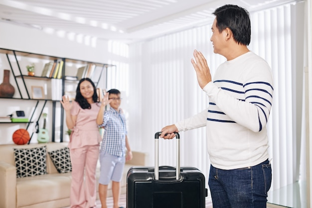 Mature asian man with suitcase waving to his wife and preteen son when leaving for business trip