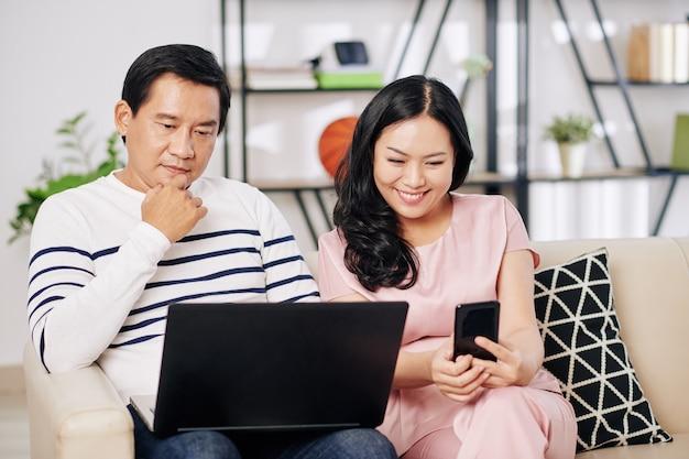 彼の妻が近くに座ってスマートフォンでビデオを見ているときにラップトップで働く成熟したアジア人男性