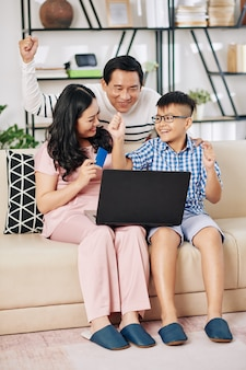 Mature asian woman buying present online for her excited husband and preteen son