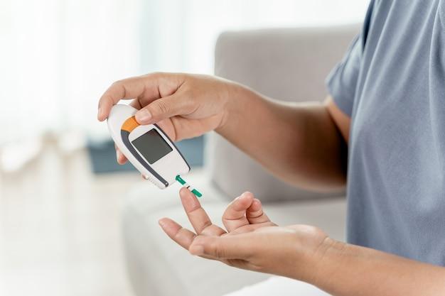 Зрелая азиатская женщина проверяет уровень сахара в крови с помощью цифрового глюкометра, здравоохранения и медицины, диабета, концепции гликемии