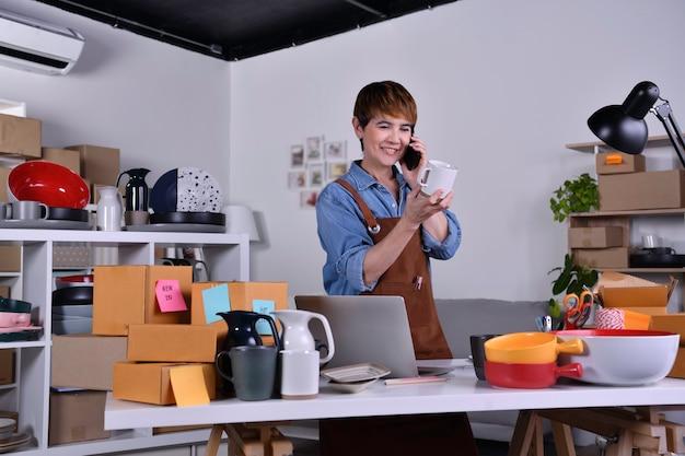 성숙한 아시아 여성 기업가, 비즈니스 소유자가 제품을 확인하고 전화로 고객과 이야기합니다. 가정 개념에서 온라인 판매 비즈니스 작업