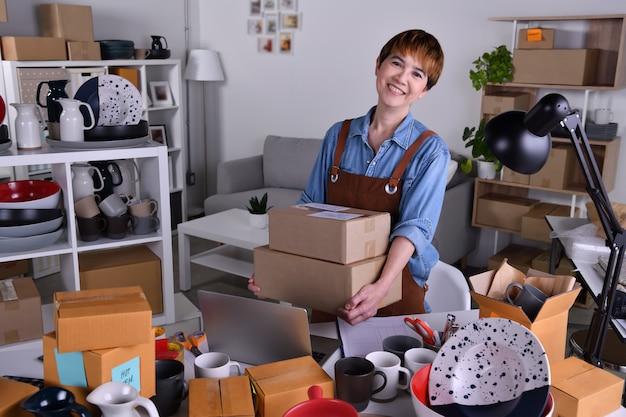 성숙한 아시아 여성 기업가, 배달 및 배송을 위해 세라믹 제품을 포장하는 사업주. 가정 개념에서 온라인 판매 비즈니스 작업