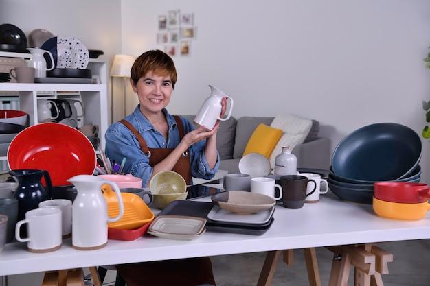 성숙한 아시아 여성 기업가/점토 세라믹 제품을 보여주고 집에서 일하는 사업가
