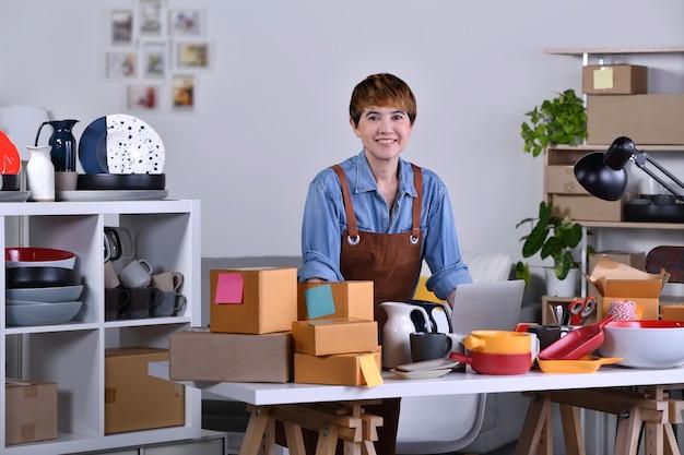 성숙한 아시아 여성 기업가, 점토 세라믹 제품으로 홈 오피스에 서서 일하는 사업가입니다. 미소와 카메라를보고