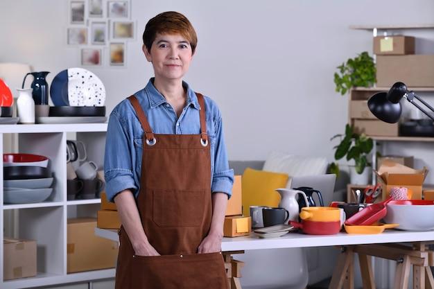 성숙한 아시아 여성 기업가/점토 세라믹 제품 앞에 서서 집에서 일하는 사업가