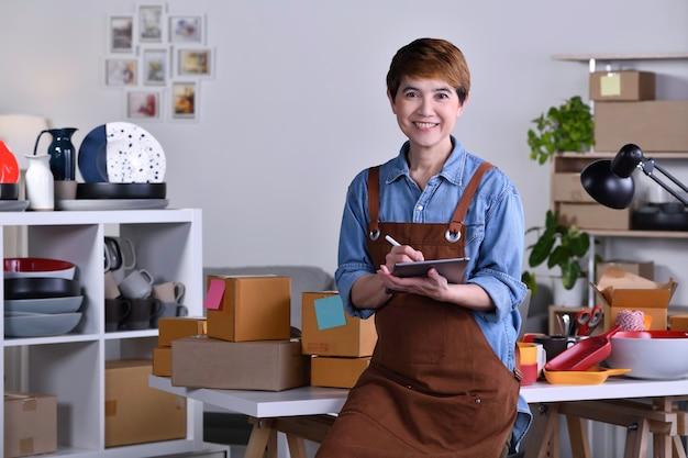 Зрелая азиатская женщина-предприниматель / владелец бизнеса, стоящая перед своим глиняным керамическим продуктом и работающая дома