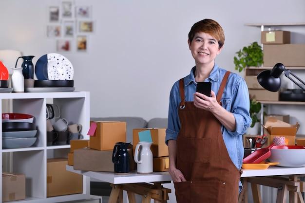 성숙한 아시아 여성 기업가, 점토 세라믹 제품 앞에 서서 집에서 일하는 사업가