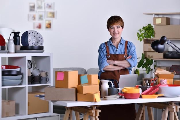 성숙한 아시아 여성 기업가, 팔짱을 끼고 서서 점토 세라믹 제품으로 홈 오피스에서 일하는 사업가입니다. 미소와 카메라를보고