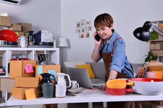 성숙한 아시아 여성 기업가, 스마트폰을 사용하여 제품을 배송하기 전에 주소와 배송 세부 정보를 확인하는 비즈니스 소유자. 가정 개념에서 온라인 판매 비즈니스 작업