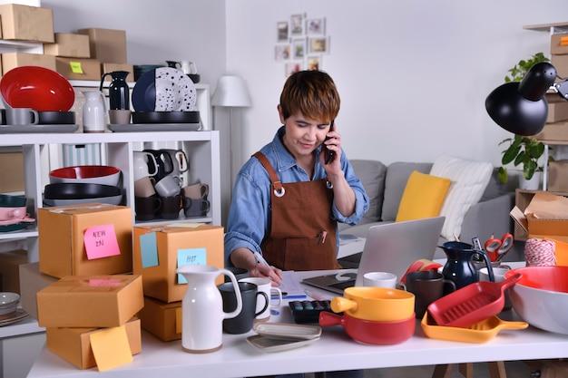 성숙한 아시아 여성 기업가, 집에서 일할 때 고객에게 제품을 배송하기 전에 스마트폰으로 주소와 배송 세부 정보를 확인하는 비즈니스 소유자