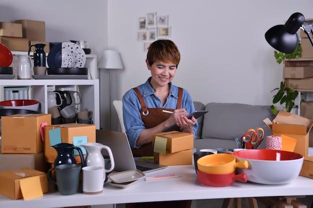 성숙한 아시아 여성 기업가, 제품을 배송하기 전에 주소와 배송 세부 사항을 확인하는 디지털 태블릿 작업을 하는 비즈니스 소유자. 가정 개념에서 온라인 판매 비즈니스 작업