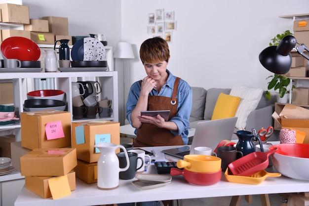 성숙한 아시아 여성 기업가, 디지털 태블릿에서 일하는 비즈니스 소유자. 가정 개념에서 온라인 판매 비즈니스 작업