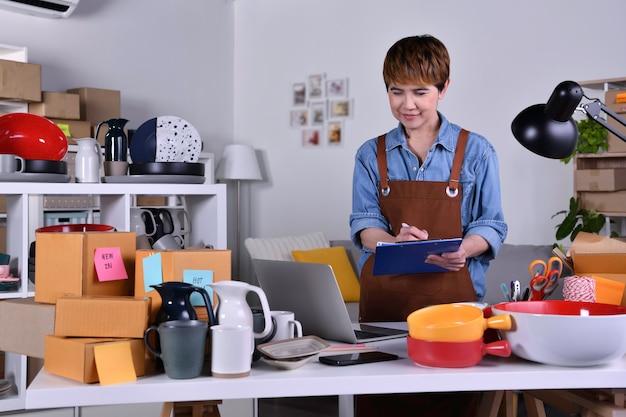 성숙한 아시아 여성 기업가, 비즈니스 소유자는 제품을 배송하기 전에 주소와 배송 세부 정보를 확인하는 노트북 작업을 합니다. 가정 개념에서 온라인 판매 비즈니스 작업