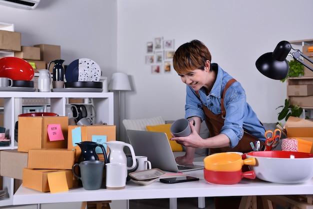 성숙한 아시아 여성 기업가, 제품을 배송하기 전에 주소와 배송 세부 정보를 확인하는 랩톱 컴퓨터 작업을 하는 비즈니스 소유자. 가정 개념에서 온라인 판매 비즈니스 작업