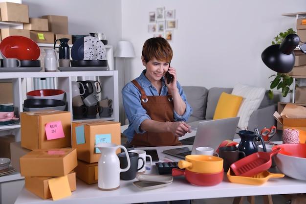 성숙한 아시아 여성 기업가, 집에서 일할 때 고객에게 제품을 배송하기 전에 주소와 배송 세부 정보를 확인하는 랩톱 컴퓨터 작업을 하는 비즈니스 소유자