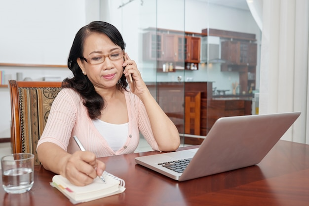 Mature asian woman sitting at table at home with laptop, talking on phone and making notes