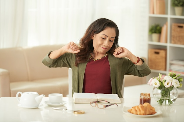 Mature asian woman stretching while sitting at breakfast table in morning