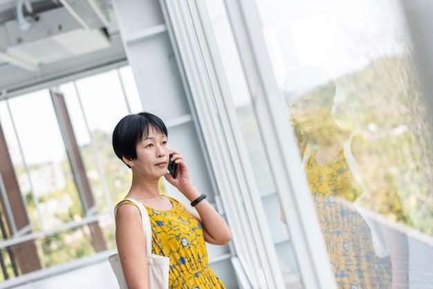 成熟したアジアの女性がモダンな建物で携帯電話で話す