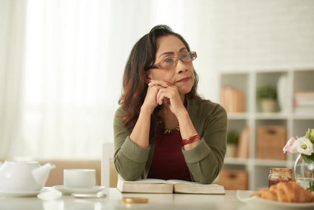 Зрелая азиатская женщина думает о чем-то, сидя за столом, глядя в сторону