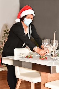 Mature asian woman with a face mask and a santa hat putting two glasses on a table