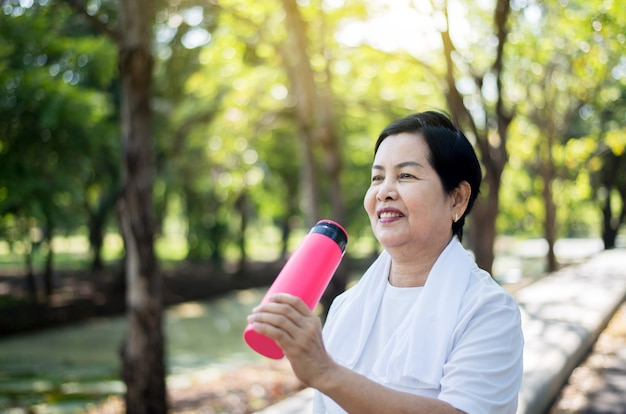 Mature asian women drinking water after break exercising at nature,healthy elderly woman concept