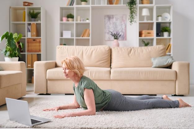 オンラインフィットネスコース中にインストラクターの後に運動を繰り返しながらノートパソコンの前に横たわっているアクティブウェアの成熟した魅力的なブロンドの女性