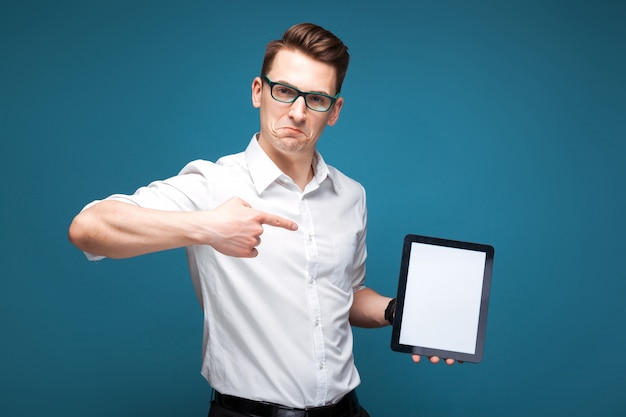 Mature attractive businessman in costly watch, black glasses and white shirt hold empty tablet