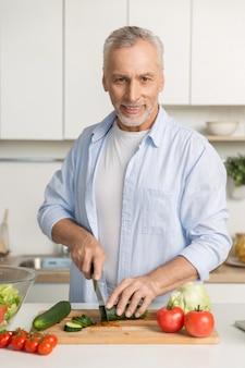 キッチンの料理に立っている成熟した魅力的な男