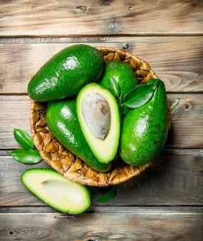 Зрелый авокадо в корзине. на коричневом деревянном.