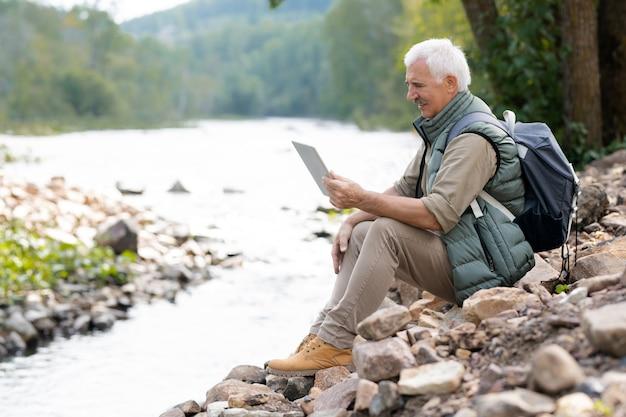 Зрелый турист с тачпадом использует видеочат для общения с женой, сидя на камнях на берегу реки