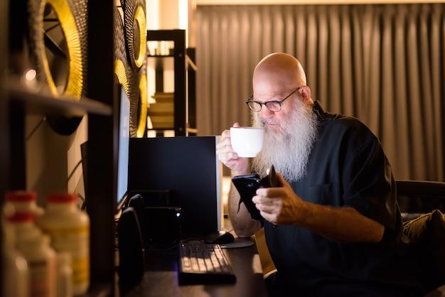 늦은 밤 집에서 초과 근무를하는 동안 커피를 마시고 전화를 사용하는 성숙한 대머리 수염 난 남자