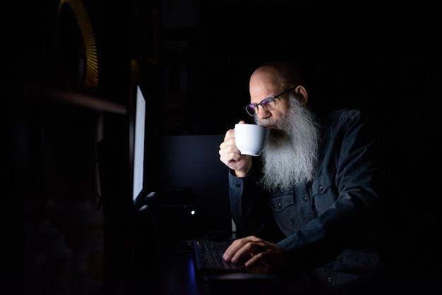어둠 속에서 집에서 초과 근무하는 동안 커피를 마시는 성숙한 대머리 수염 남자