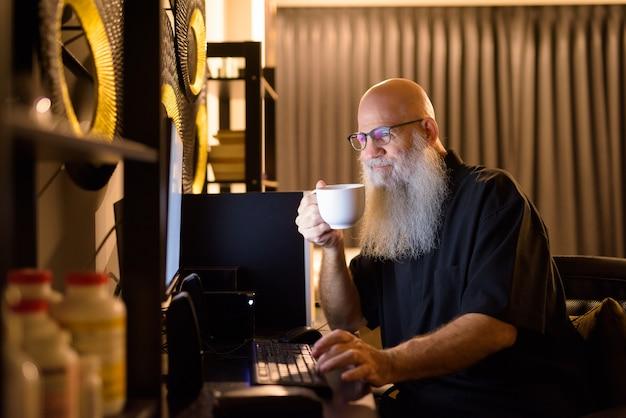 늦은 밤 집에서 초과 근무를하는 동안 커피를 마시는 성숙한 대머리 수염 남자