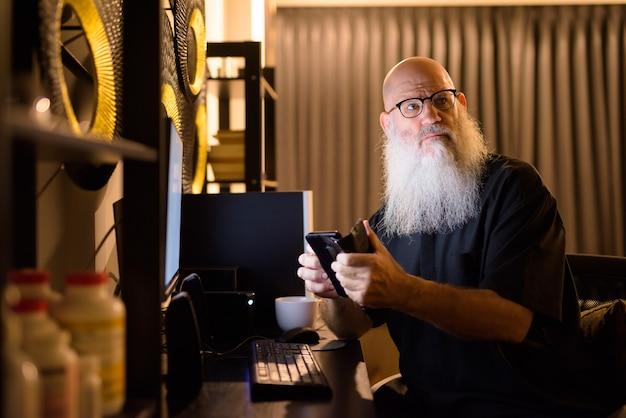 成熟したハゲのひげを生やした男性が自宅で夜遅くまで残業しながら考えて電話を使用