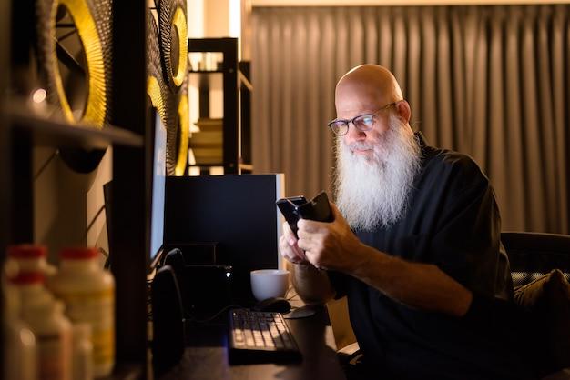 成熟したハゲのひげを生やした男性が夜遅くまで家で残業しながら電話を使用して